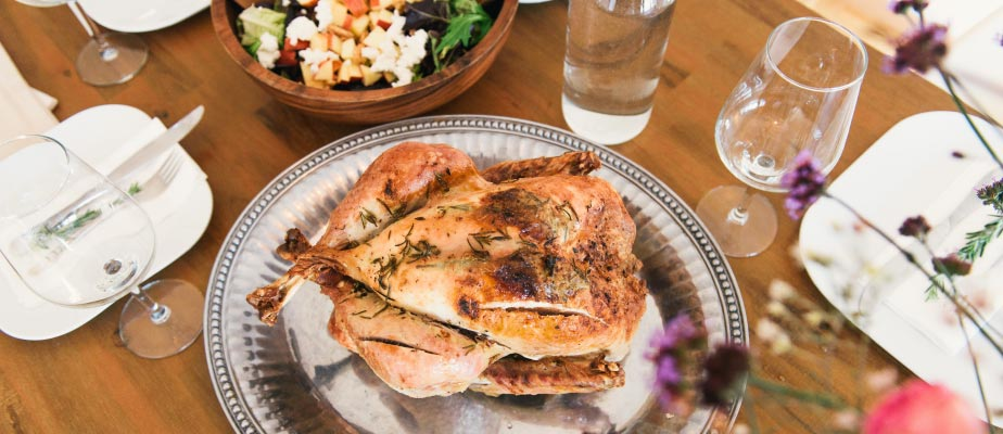 Aerial view of a Thanksgiving turkey on a silver platter next to water glasses and a green salad