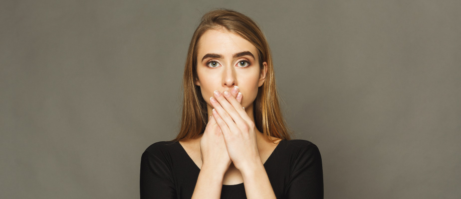 Blonde woman wearing a black shirt covers her mouth with her hands because she is embarrassed about her overbite