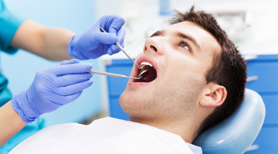 Brunette man sits in a dental chair as a dental hygienist examines his mouth with modern dentistry tools