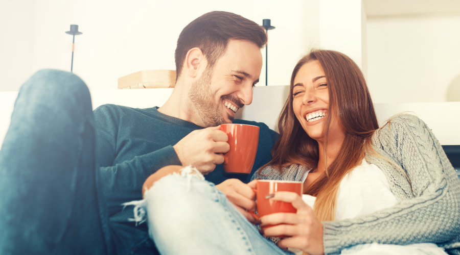 Man and woman with dental implants and veneers smile as they cuddle on the couch with orange mugs