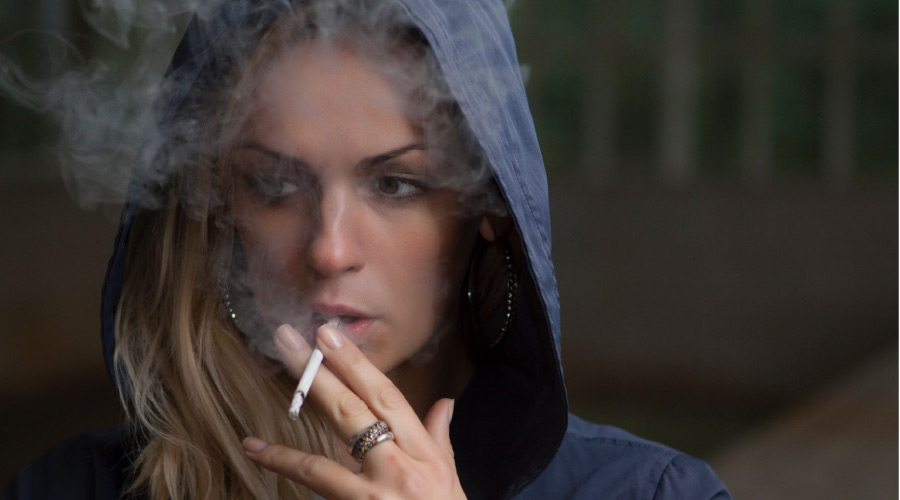 woman wearing a hoodie smoking a cigarette