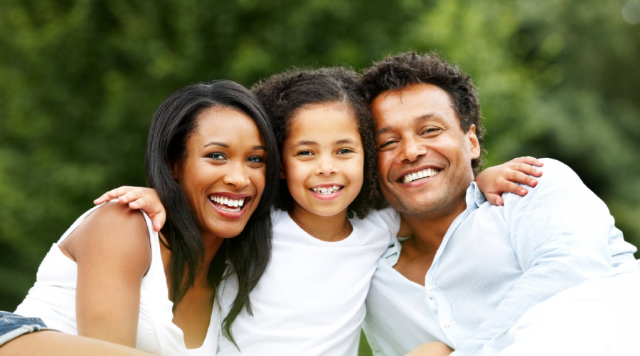 Black mother, daughter and father smiling in front of green trees