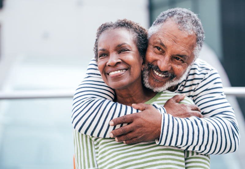 Smiling older black couple with the man standing behind the woman and enfolding her in his arms