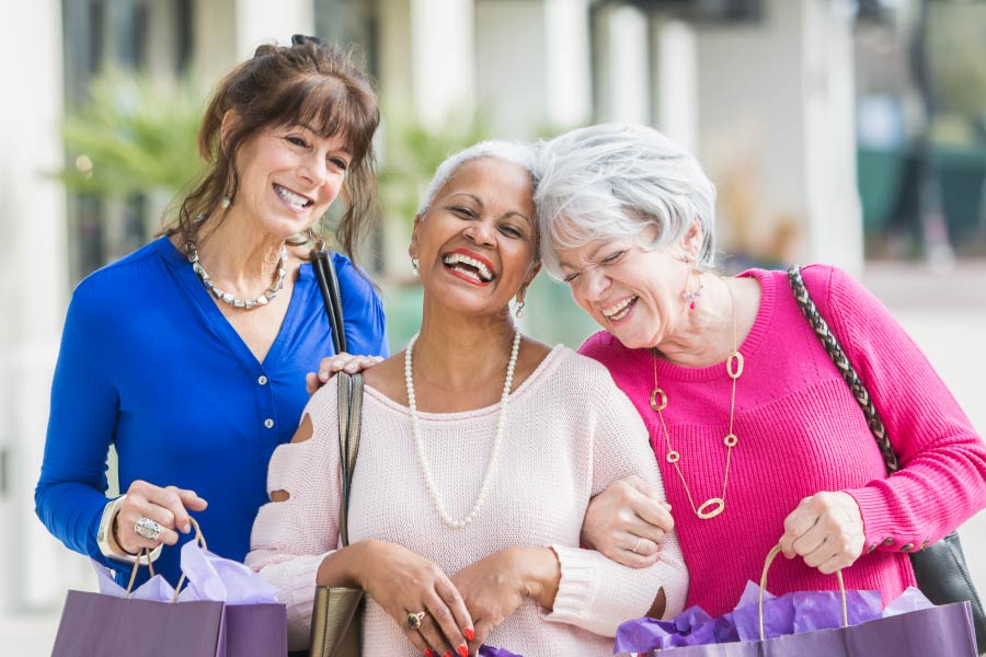 Three older ladies with linked arms, smiling and shopping together