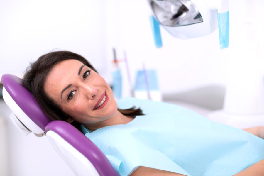 Smiling brunette woman looking sideways from the dental chair