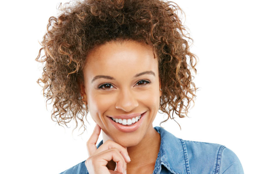 Smiling young adult woman with dark curly hair.