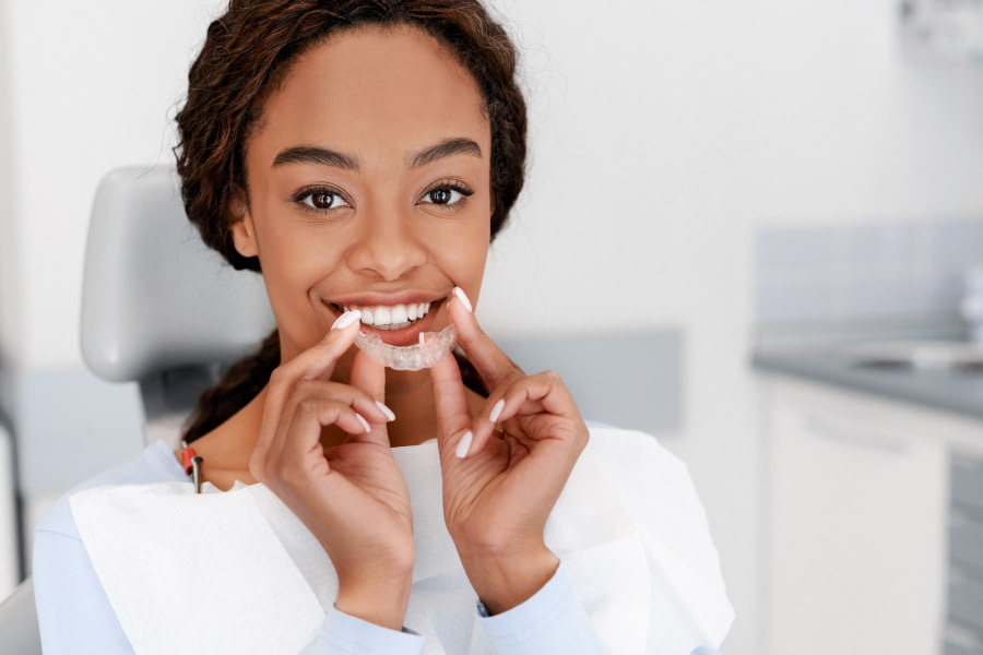 Pretty black girl is holding a ClearCorrect® clear aligner in front of her smile.